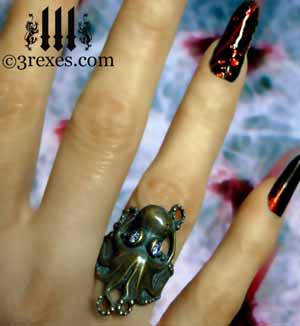 brass octopus dream ring with pink cz stones invokes a steampunk feel on model ice background